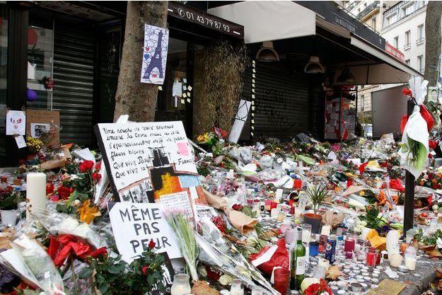 """Des fleurs et des bougies devant le bar """"La Belle Equipe""""."""