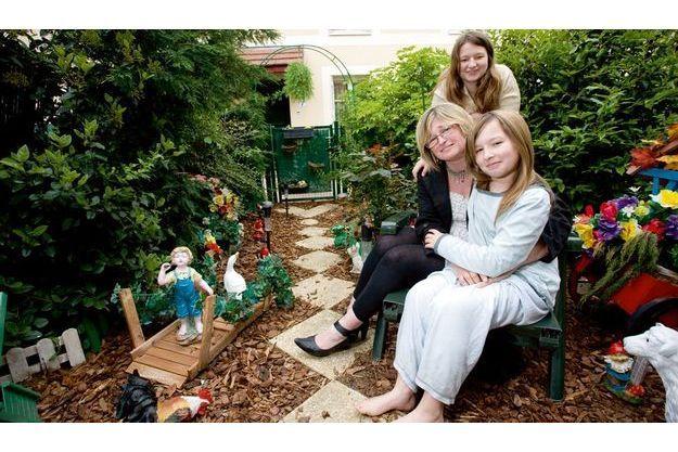 Josette avec ses filles Laura, 15 ans, et Léa, 9 ans.  Ensemble, elles ont  peuplé leur jardin de nains et autres figurines du monde merveilleux de Disney.