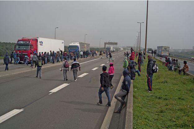 Des migrants à l'assaut des camions sur l'autoroute qui mène au port de Calais, mercredi 17 septembre. Certains bloquent les poids lourds et retournent leur rétroviseur pour empêcher les chauffeurs de voir ce qui se passe à l'arrière.