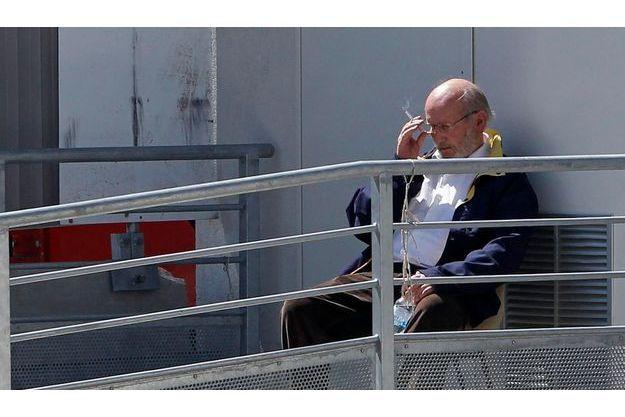 Pendant une suspension d'audience, Jean-Claude Mas fume une cigarette devant le palais de Justice de Marseille, le 17 avril.