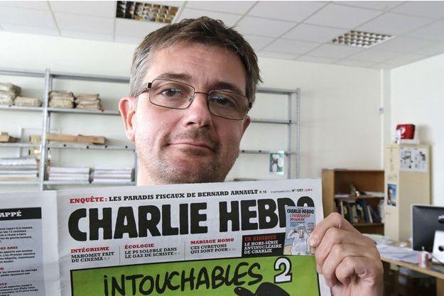 """En septembre 2012, Charb pose avec une Une de """"Charlie""""."""