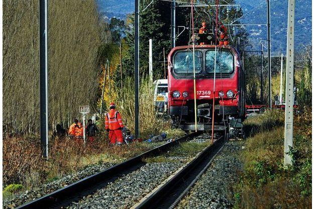 Agents de la SNCF et gendarmes examinent les débris autour de la locomotive du TER, samedi 16 décembre.