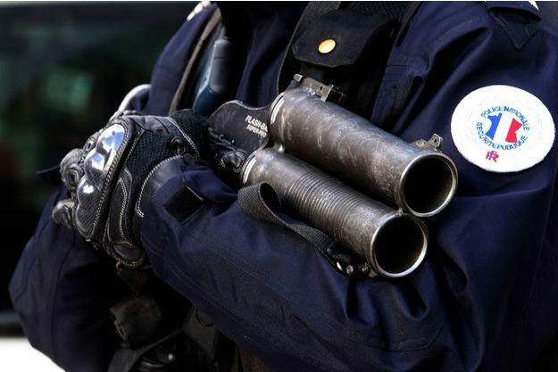 Un policier tient un flash-ball devant le tribunal de Reims après les incident entre supporters bastiais et des policiers à Reims.