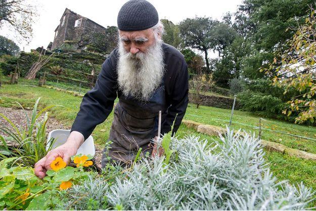 Frère Jean dans son jardin de plantes arômatiques. Derrière lui, le skite Sainte-Foy, restauré par le moine, accueille ses hôtes dans le silence.
