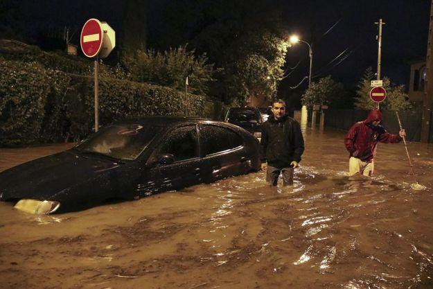 Dans la nuit du 3 octobre 2015, deux hommes dans une rue de Cannes La Bocca, de l'eau jusqu'aux cuisses, devant une voiture englouties par les flots.
