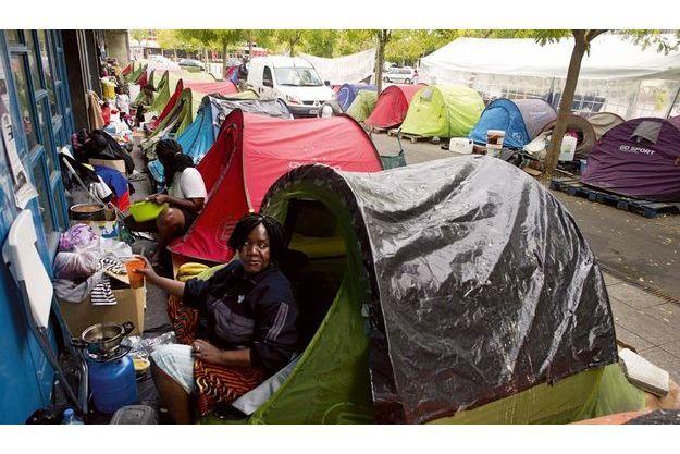 Place de la Fraternité, à La  Courneuve, 10 heures du matin.  Les femmes se mettent  à la cuisine sur des réchauds de  camping, pendant que les hommes  discutent, un peu plus loin.