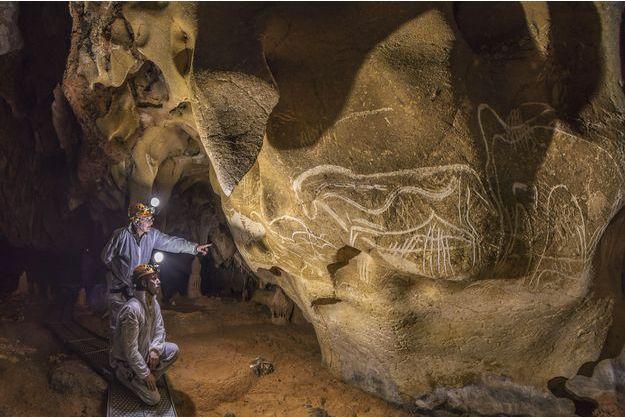 Dans la Salle Hillaire, devant le panneau des Grandes Gravures, le préhistorien Jean Clottes, directeur scientifique de la Grotte Chauvet de 1998 à 2006 et David Huguet, membre du comité scientifique de la Grotte Chauvet observent le panneau du Cheval Gravé.