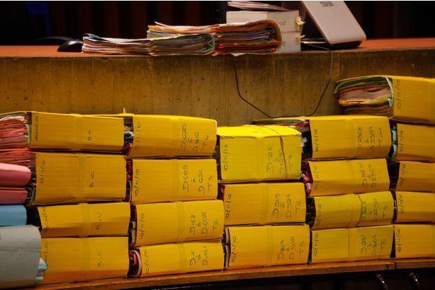 La salle d'audience où se tient le procès et les épais dossiers des procès-verbaux.