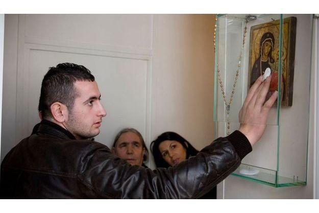 Un pélerin, espérant attraper une des «larmes» de la Vierge, passe précautionneusement un coton sur l'icône.