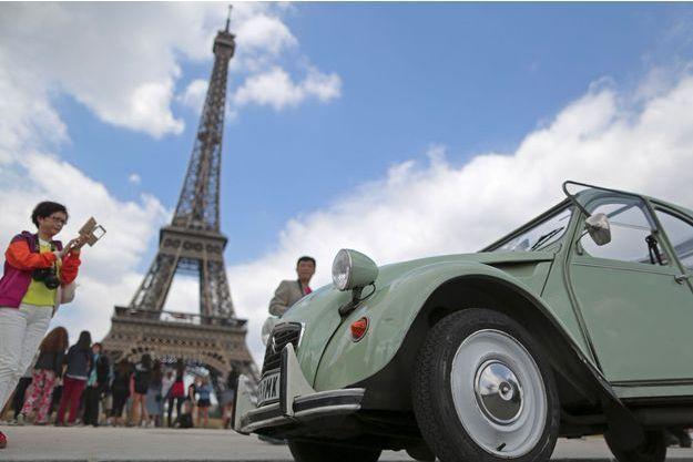 Une Citröen 2CV devant la Tour Eiffel.