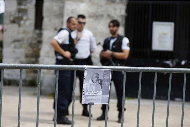 Des policiers et le portrait du père Hamel devant l'église de Saint-Etienne-du-Rouvray.