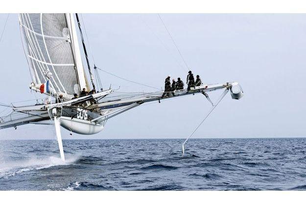 Cinq hommes au pied du mât. Cinq hommes sur le bras de liaison. C'est l'équipage pour les tests. Fixé au flotteur, le foil sert d'aile à «L'Hydroptère».