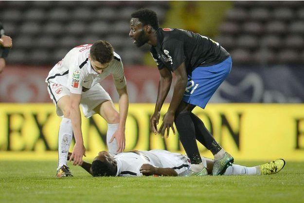 Patrice Ekeng, effondré sur le terrain, vendredi soir, entouré de ses camarades.