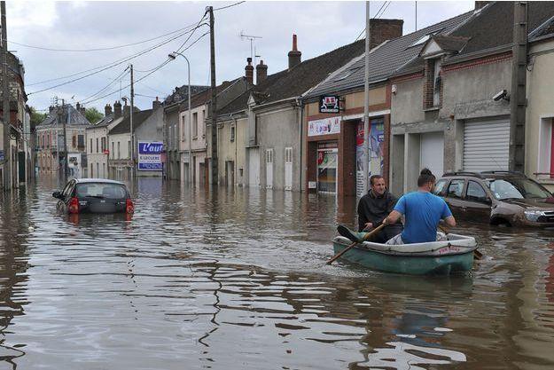 Des résidents de Montargis traversent une rue sur une barque.
