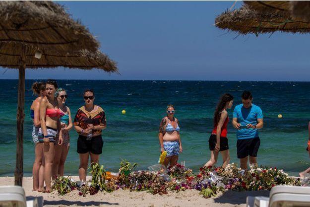 Des touristes devant les fleurs déposées sur la plage de Sousse en mémoire des victimes de l'attentat.