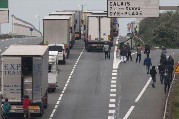 Des migrants tentent d'entrer dans des camions aux abords de Calais, en octobre.