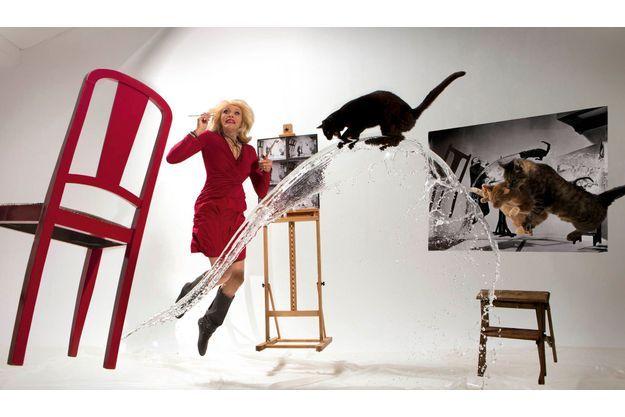 Amanda Lear prend la place de Salvador Dali pour une  reconstitution de «Dali Atomicus», la célèbre photo du maître prise en 1948 par son ami le photographe Philippe Halsman.