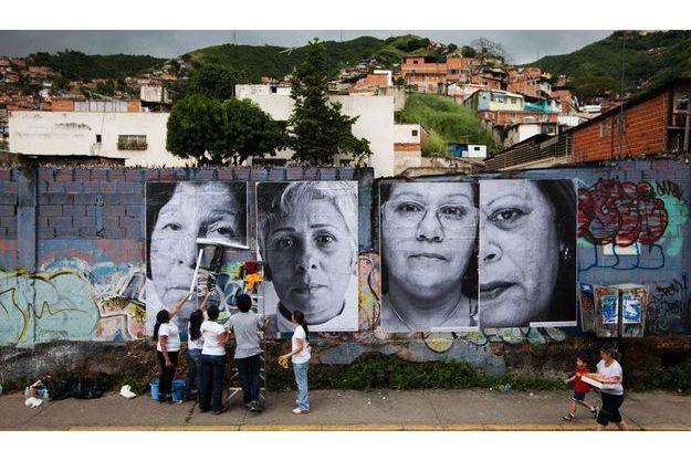 """Novembre 2011: des volontaires collent une cinquantaine de portraits sur les murs des quartiers pauvres de Caracas dans le cadre du projet """"Esperanza"""" et du projet mondial """"Inside Out"""" de l'artiste JR."""