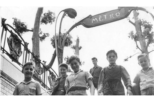 Le métro à Paris en 1950. Groupe d'écoliers, cartables en main, descendant les escaliers de la station de métro Mirabeau (ligne 10).