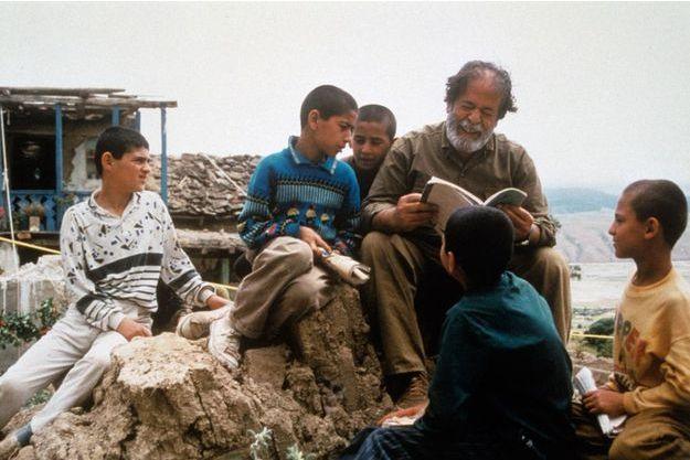 """Une photo qui résume parfaitement l'oeuvre d'Abbas Kiarostami: un vieil homme qui fait la lecteur aux enfants dans """"Au travers des oliviers"""""""