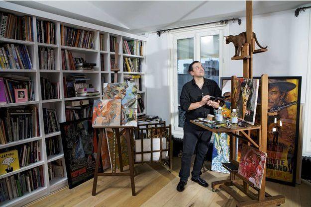 Sous le regard d'un de ses chats,  il dessine sur sa tablette, le 14 janvier. Dans son appartement parisien, parmi ses toiles.