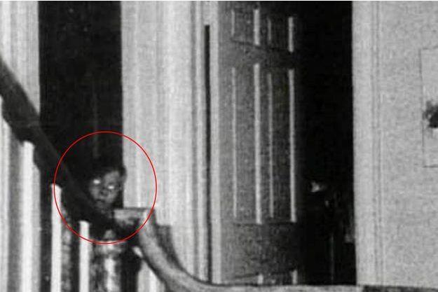 Maison d'Amityville (Etat de New York). Sur ce cliché pris en 1976, un visage aux yeux effrayants. Il s'agirait de l'un des enfants assassinés par le jeune Ronald De Feo.
