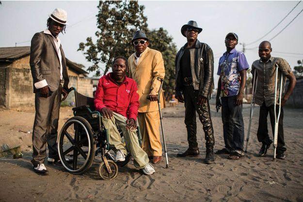Le Staff à N'Djili, devant la maison de Papa Ricky (en costume jaune), le leader du groupe.