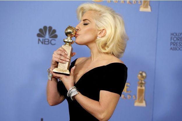 Lady Gaga pose avec son Golden Globe après la cérémonie.