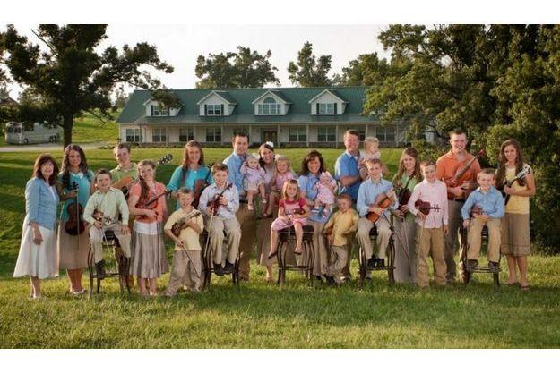 Les duggar posent pour un portrait de famille devant leur domicile, en 2010