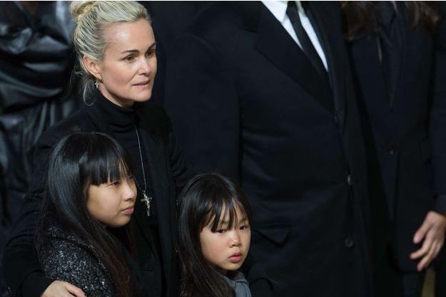Entourée de ses filles Jade et Joy, Laeticia Hallyday le jour de l'hommage à Johnny à la Madeleine, le 9 décembre 2017. Elle porte alors le désormais célèbre pendentif.