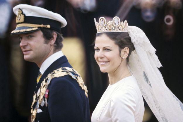 Le roi Carl XVI Gustaf coiffé d'une casquette, aux côtés de Silvia Sommerlath, portant une robe Dior et coiffée d'un diadème d'or orné de camées sertis de perles fines, à l'occasion de leur mariage, le 19 juin 1976.