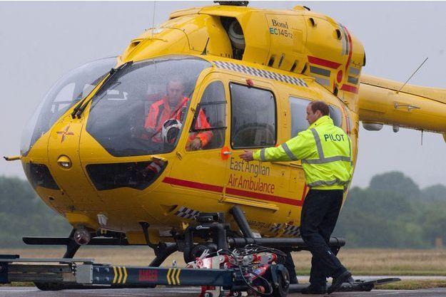 Le prince William photographié avec l'hélicoptère-ambulance d'Air Ambulance East Anglian qu'il pilote, le 13 juillet 2013.
