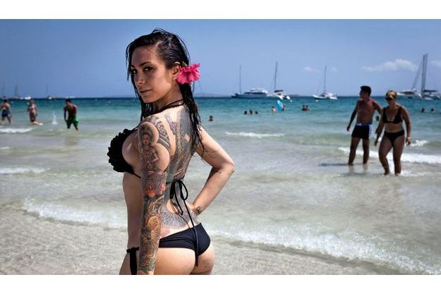 Aux Salines, à Ibiza, Lara, 27 ans, infirmière madrilène, expose ses grigris : un bouddha, un tigre et un long serpent sur le dos.