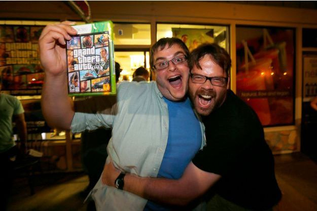 En Californie mardi à minuit, l'un des animateurs qui a travaillé sur le jeu, Michael Petterson, étreint Casey, un fan de GTA qui vient de s'offrir GTA V.