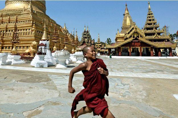 Un moinillon court à Mandalay devant la pagode Kuthodaw et son stupa d'or haut de 60 mètres.