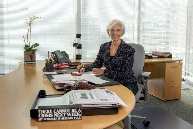 """Christine Lagarde dans son bureau, à Washington. Devant sa bannette, un message humoristique : """"Il ne peut y avoir de crise la semaine prochaine, mon agenda est déjà plein."""""""