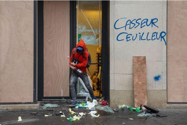 Un casseur pille un magasin place Saint-Augustin, à Paris, le 8 décembre.