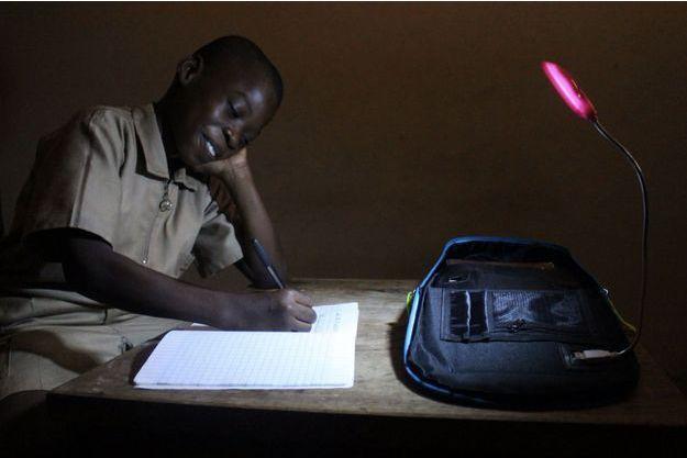 Un écolier étudiant chez lui éclairé par son Solarpak.