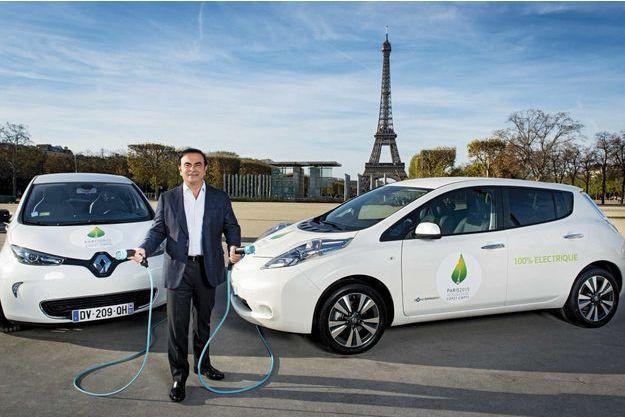 Carlos Ghosn, P-DG de Renault-Nissan, et les deux voitures électriques officielles de la Cop21 : la Renault ZOE (à g.) et la Nissan Leaf. Dans ses mains, ce qui remplacera la pompe à essence.