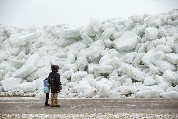 Une femme et sa fille devant le mur de glace qui s'est formé ce week-end à Fort Erié.
