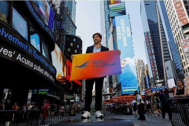 """Javier Bardem brandit une pancarte """"Protect the oceans"""" à Times Square à New York, le 19 août."""