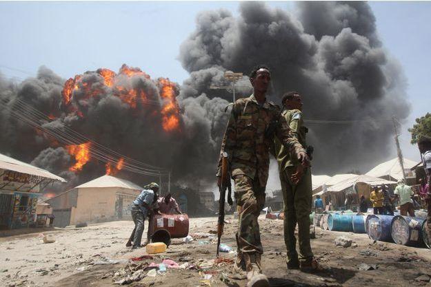 Mogadiscio, en Somalie, février 2015. Suite à une explosion dans une station-service, les civils éloignent les barils de pétrole à proximité d'un marché en plein air.