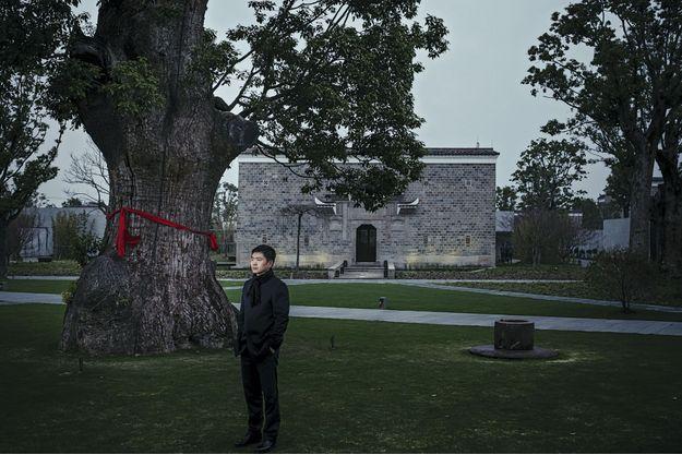 A 25 km du centre de Shanghai, l'homme d'affaires pose sous le plus vieux camphrier promis à la disparition dans un lac de retenue. Placé au centre du domaine hôtelier qu'il a créé, l'arbre reçoit sa visite quotidienne.