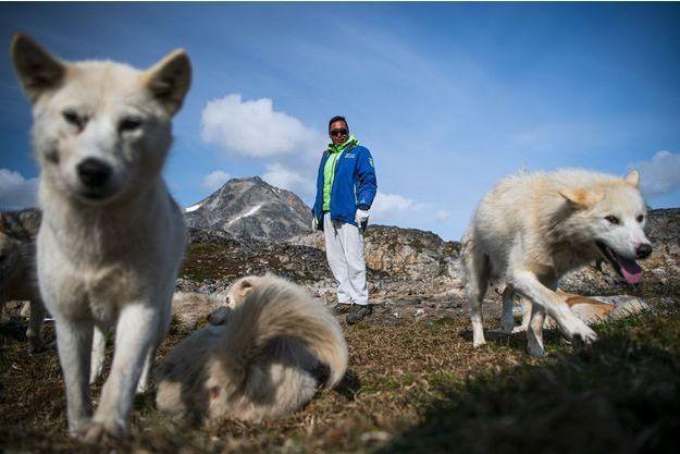 A Kulusuk, un village insulaire du Groenland, un chasseur pose avec son chien, devant un paysage sans glace.