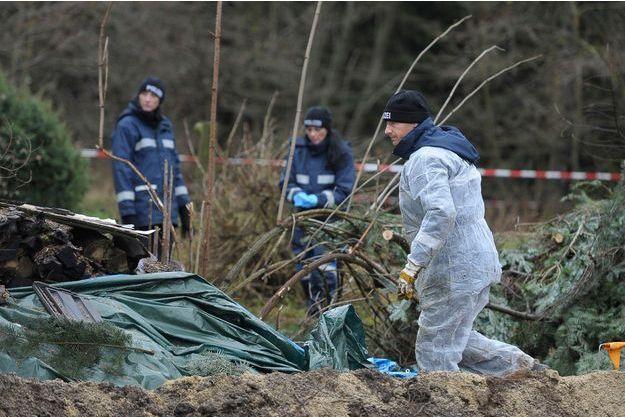 La police inspecte le jardin où ont été enterrés les bouts de corps de la victime.