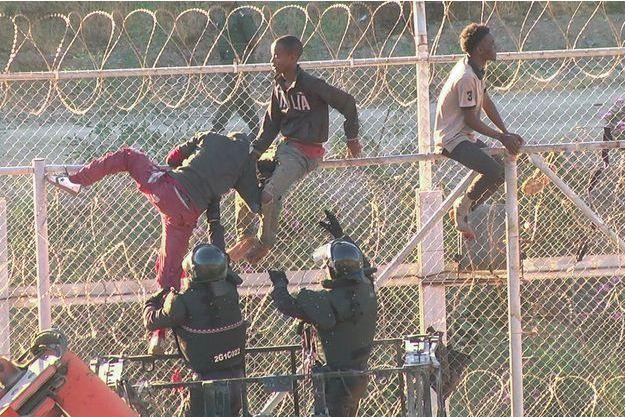 Des migrants escaladent la clôture pour entrer dans l'enclave espagnole de la Ceuta, au Maroc.