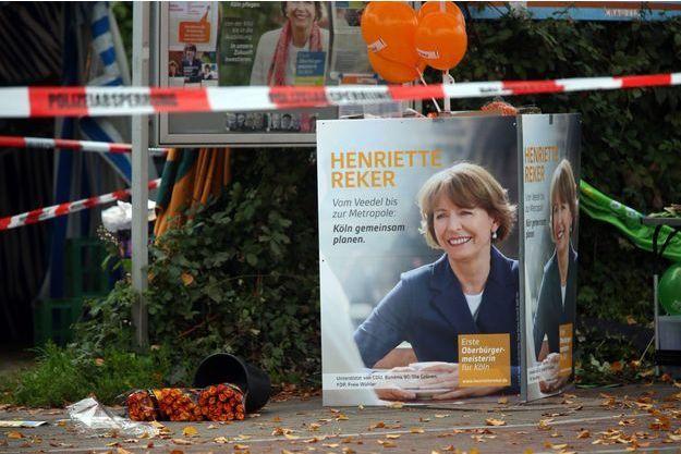 Sur les lieux de l'attaque, samedi, à Cologne. Sur l'affiche, la candidate à la mairie de la ville, Henriette Reker, une des victimes.