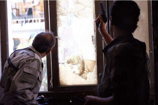 Ahmed, un jeune avocat chef d'une section rebelle, dégaine son pistolet pendant des combats dans le quartier de Cheikh Maqsoud, au nord d'Alep, le 25 avril 2013.