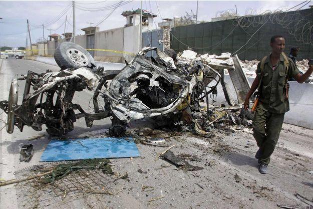 Un soldat somalien près de l'épave d'une voiture piégée devant les locaux de l'ONU à Mogadiscio.