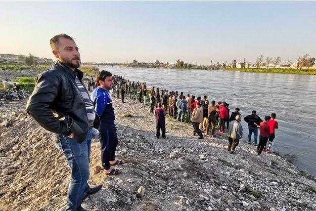 Des centaines de personnes massées au bord de l'eau suivant les recherches